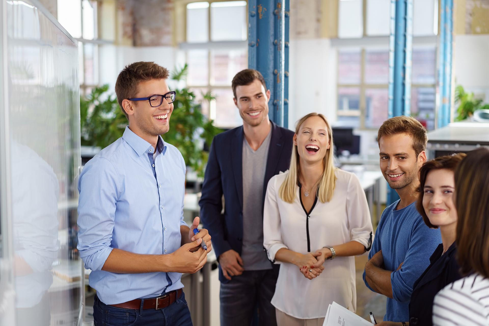 Nauravia toimistotyöntekijöitä valkoisen tussitaulun äärelllä, pienessä toimistossa