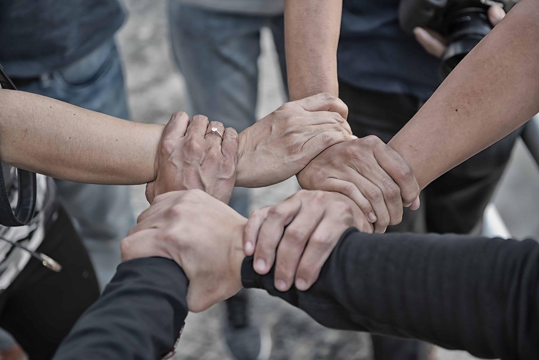 ryhmä ihmisiä ympyrässä kädet keskellä toisiaan ranteesta kiinni muodostaen neliön